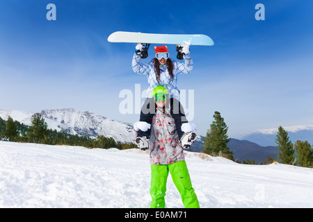 Man in ski mask holding girl with board up head - Stock Photo