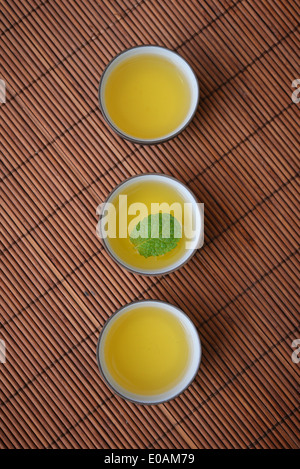 Green tea in cups with mint on bamboo mat - Stock Photo