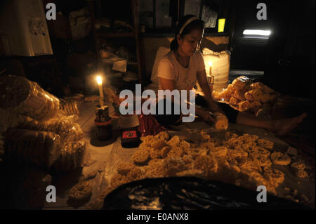 Jakarta, Indonesia. 7th May, 2014. Women packages crackers beside candles because of power outage in southern Jakarta, - Stock Photo
