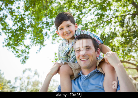 Mixed Race Father and Son Playing Piggyback Together in the Park. - Stock Photo