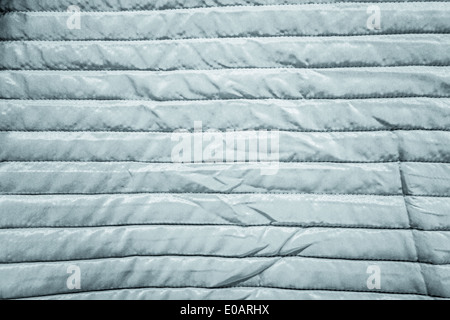 detail of a warm and striped quilt crumpled in some points - Stock Photo