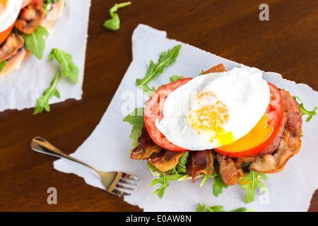 Open-faced BLT sandwich with provolone cheese, arugula, bacon, tomato and a fried egg on sweet potato bread - Stock Photo