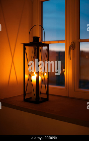 Lantern with lighted candle on window sill  at dusk - Stock Photo