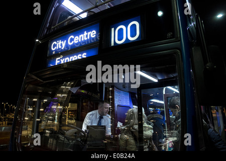 People board the bus that makes the route Airport - City Center, Edinburgh. - Stock Photo