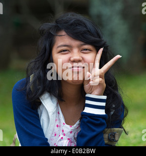 Young girl showing the victory sign Bali Indonesia - Stock Photo