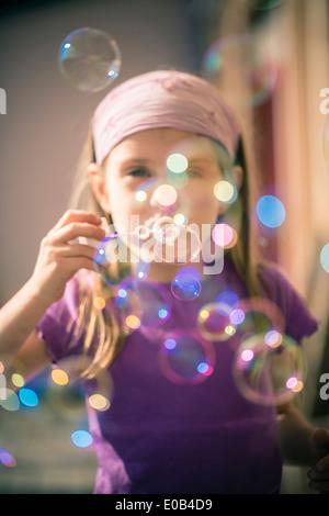 Portrait of little girl blowing soap bubbles - Stock Photo