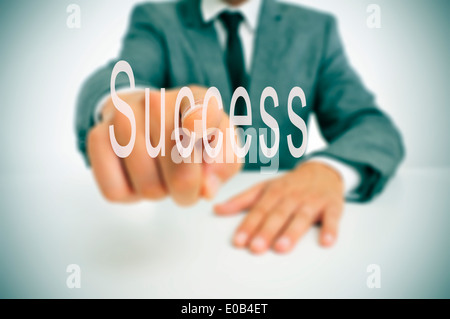 businessman sitting in a desk pointing the finger to the word success written in the foreground - Stock Photo
