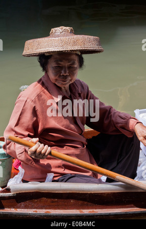A Woman on her boat at The Floating Market at Damnoen Saduak, Bangkok, Thailand - Stock Photo