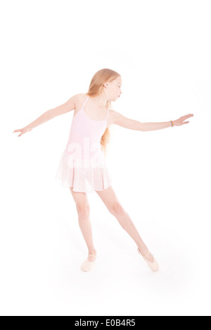 girl dancing in pink ballet suit in studio with white background - Stock Photo