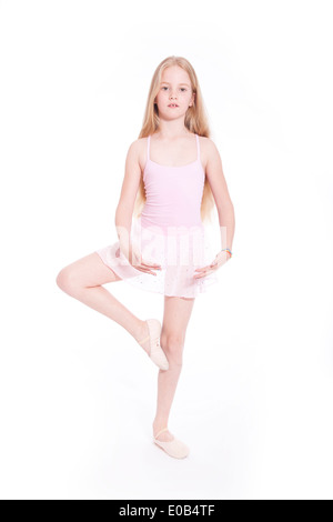 young girl dancing in pink ballet suit in studio with white background - Stock Photo