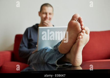Mid adult man relaxing on sofa engrossed in laptop - Stock Photo