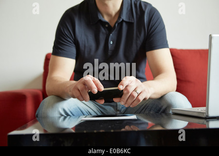 Mid adult man holding smartphone with digital tablet and laptop on table - Stock Photo