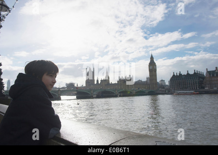 Boy by River Thames, Palace of Westminster in background, London - Stock Photo