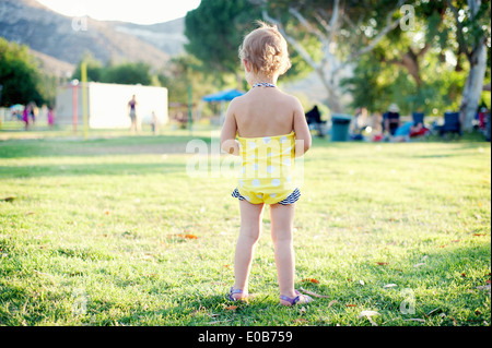 Rear view of female toddler standing in park field - Stock Photo
