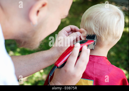 Father cutting toddler sons hair with clippers - Stock Photo