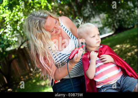 Mother cutting toddler sons hair with clippers - Stock Photo