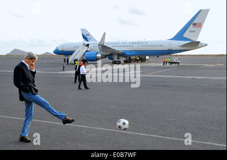 US Secretary of State John Kerry kicks a soccer ball as he waits for his Air Force jet to be refueled during a stop - Stock Photo
