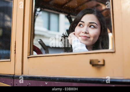 Portrait of young woman, looking through window of cable car - Stock Photo
