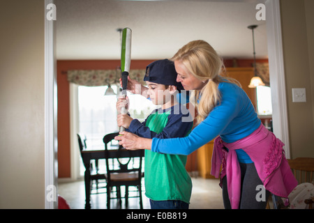 Mother teaching son to hold a baseball bat - Stock Photo