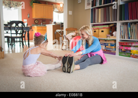 Mother and young daughter warming up for ballet in sitting room - Stock Photo