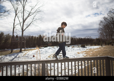 Boy walking along top of fence in park - Stock Photo