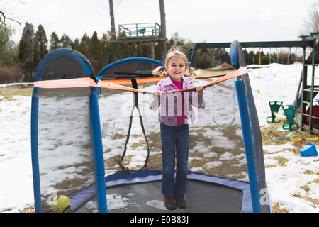 Portrait of young girl jumping on trampoline in park - Stock Photo