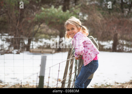 Young girl climbing wire fence in field - Stock Photo