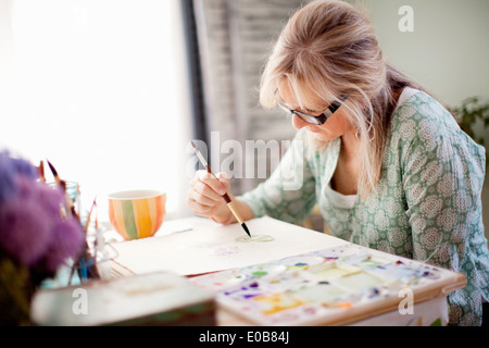 Mature female artist watercolour painting in studio - Stock Photo