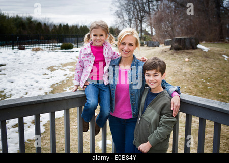 Portrait of mother and two children in park - Stock Photo