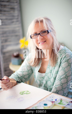 Portrait of mature female artist watercolour painting in studio - Stock Photo