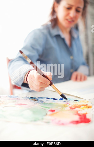 Mature woman artist painting watercolour in studio - Stock Photo
