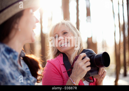Two mature women with digital camera in forest - Stock Photo