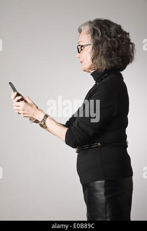 Senior woman using smartphone - Stock Photo