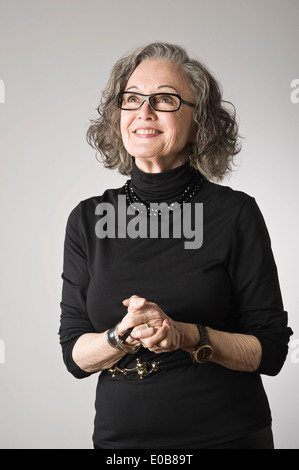 Portrait of senior woman, looking up - Stock Photo