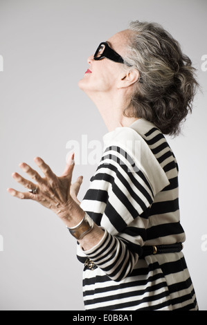 Portrait of senior woman, arms open, side view - Stock Photo