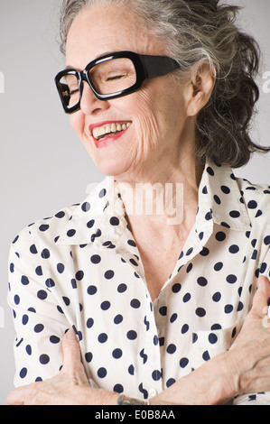 Portrait of senior woman, arms crossed, laughing - Stock Photo