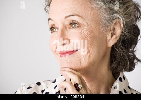 Portrait of senior woman, hand on chin, smiling - Stock Photo