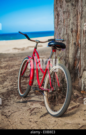 Red bicycle parked on beach, Kaua'i, Hawaii, USA - Stock Photo