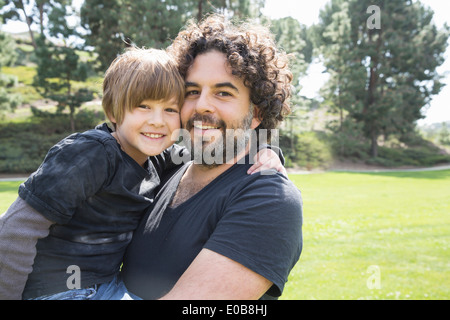 Portrait of proud father and son in park - Stock Photo