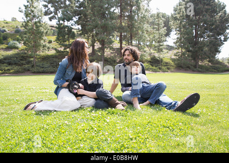 Family with two boys and dog sitting in park - Stock Photo