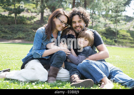 Portrait of family with two boys and dog sitting in park - Stock Photo