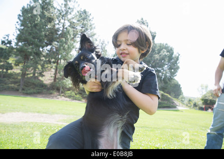 Young boy in park playing with his dog - Stock Photo