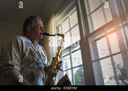 Mature man at home playing saxophone