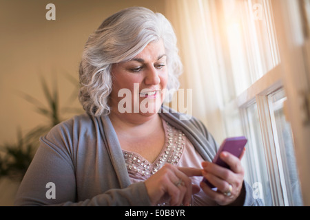 Mature woman at home texting on her cellphone - Stock Photo