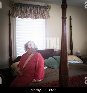Unhappy mature woman sitting on bed - Stock Photo