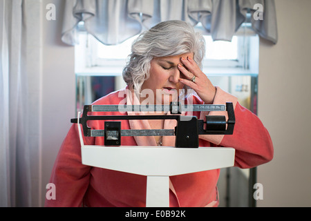 Unhappy mature woman on bathroom weighing scales - Stock Photo
