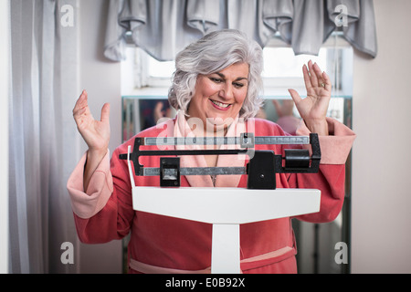 Happy mature woman on bathroom weighing scales - Stock Photo