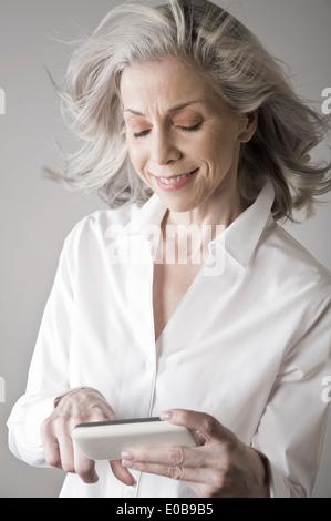 Mature woman using smartphone - Stock Photo