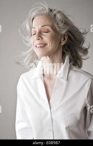 Mature woman smiling, eyes closed - Stock Photo