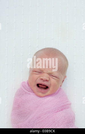 Baby crying, wrapped in blanket - Stock Photo